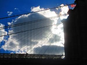 Ponte di Brooklyn, nuvole e bandiera americana